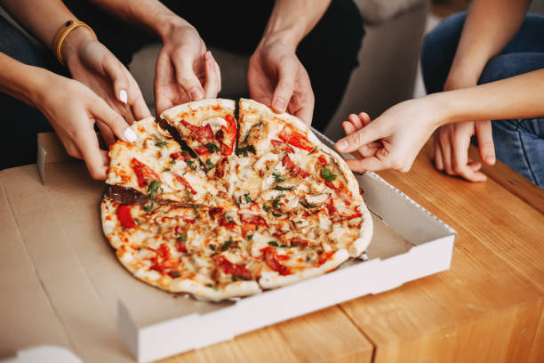 Hands of young people taking pizza slices stock photo