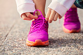 Hands of young woman lacing pink sneakers