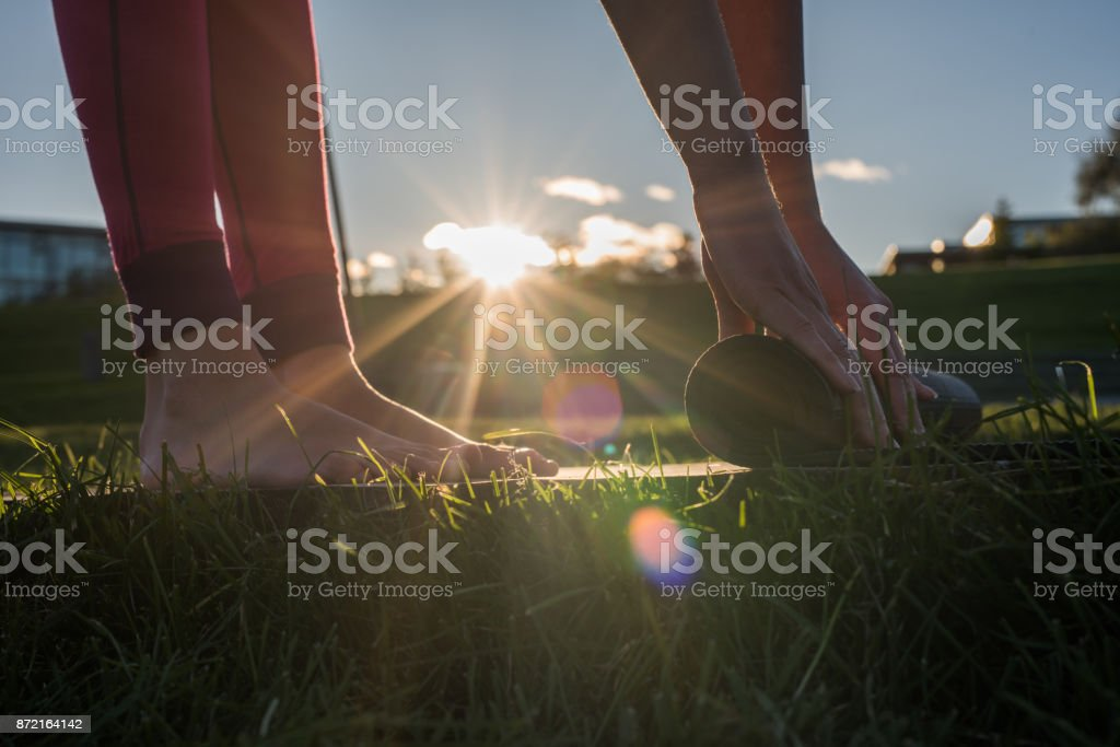 Hands of young woman rolling out exercise mat. stock photo