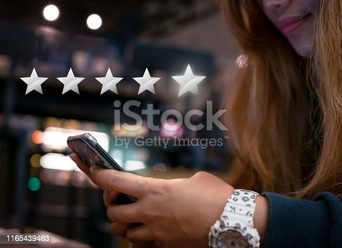 Woman internet shopping on smartphone submitting 5 silver star satisfaction feedback - Millennial girl reply to customer experience survey questions by email - Review, success & retention concept