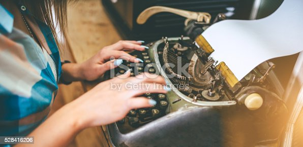 hands of young woman writer typing on antique typewriter