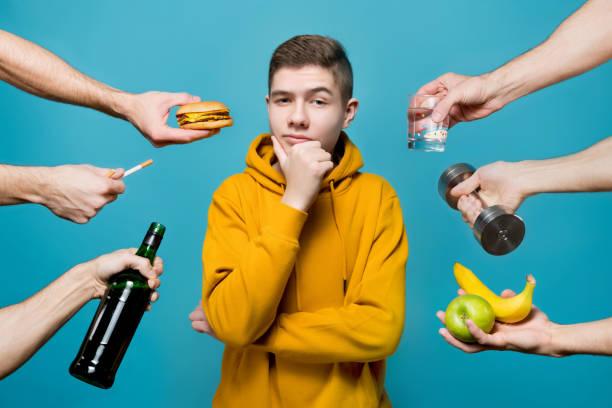 Las manos ofrecen cigarrillos, alcohol, frutas, agua de diferentes direcciones a un niño sonriente - foto de stock