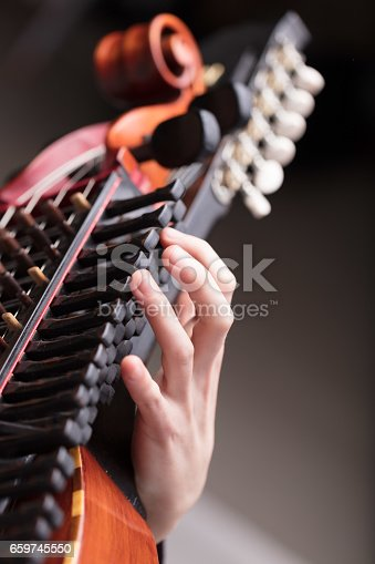 hands of a nyckhelharpor playing this handcrafted ancient traditional Swedish musical instrument, used in a folk concert or dance party