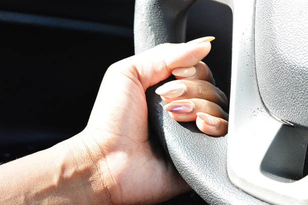 hands on a steering wheel as the light shines in the car - deign stock pictures, royalty-free photos & images