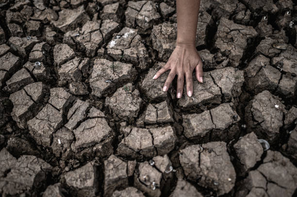 Hands on dry ground,Global warming and water crisis stock photo