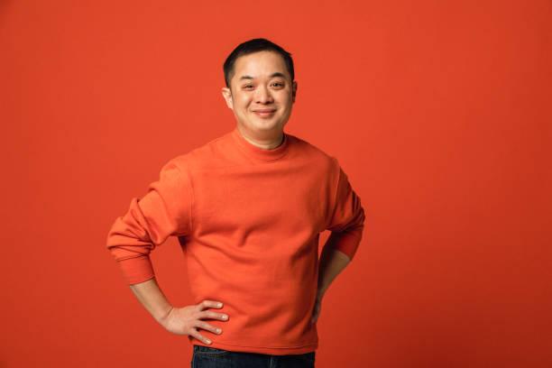 Hands On Hips Portrait of a smiling middle aged man of Chinese ethnicity. He has his hands on his hips and is standing in front of an orange coloured background. background color stock pictures, royalty-free photos & images