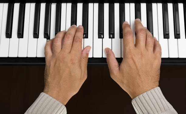 Hands on Piano Keyboard stock photo