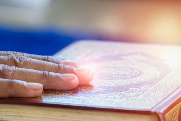 Manos en el Corán. - foto de stock