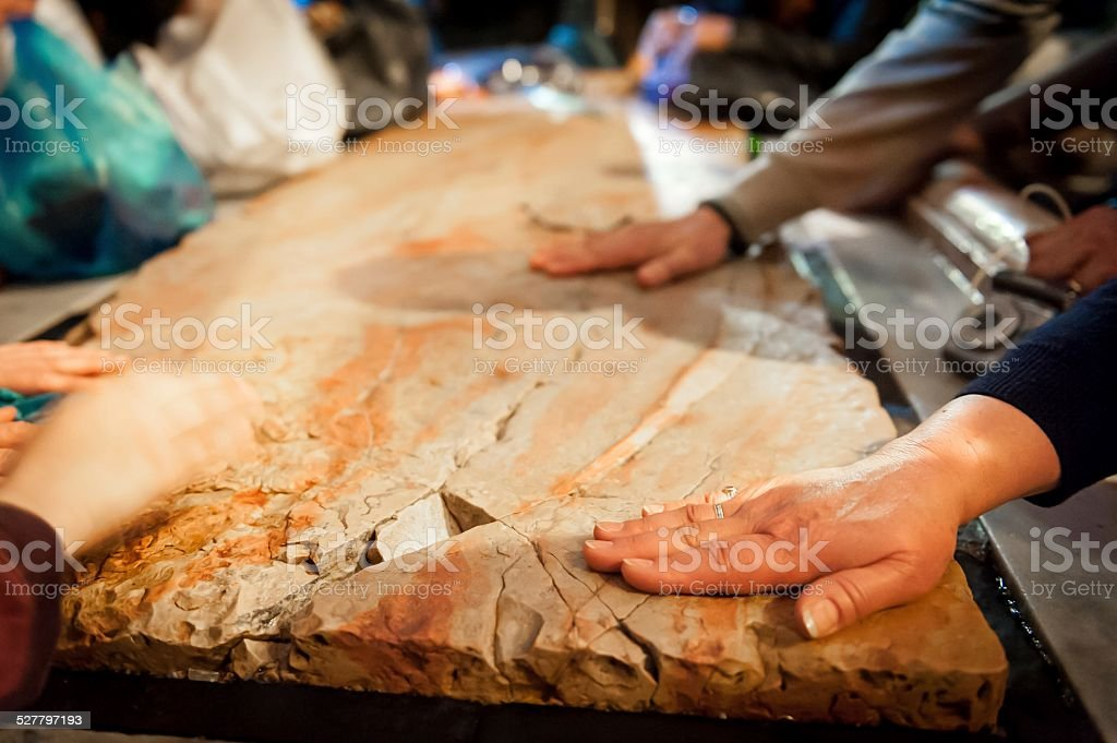 Hands on the stone of the Anointing stock photo