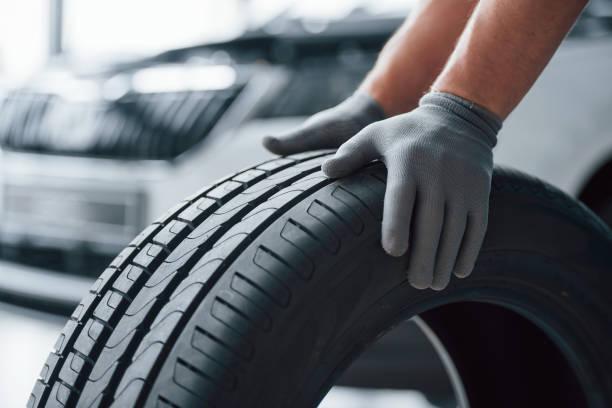 Nur Hände. Mechaniker hält einen Reifen in der Werkstatt. Austausch von Winter- und Sommerreifen – Foto