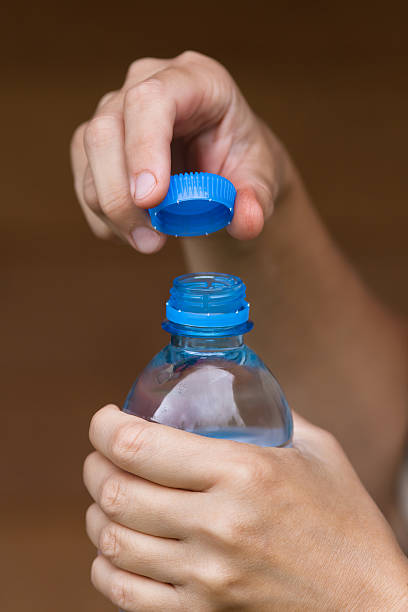 hands opening bottle with fresh water, closeup - plastic cap stock pictures, royalty-free photos & images
