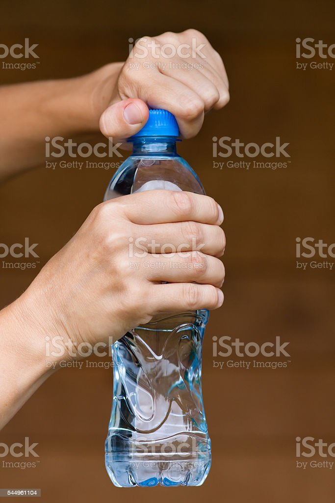 hands opening bottle with water stock photo
