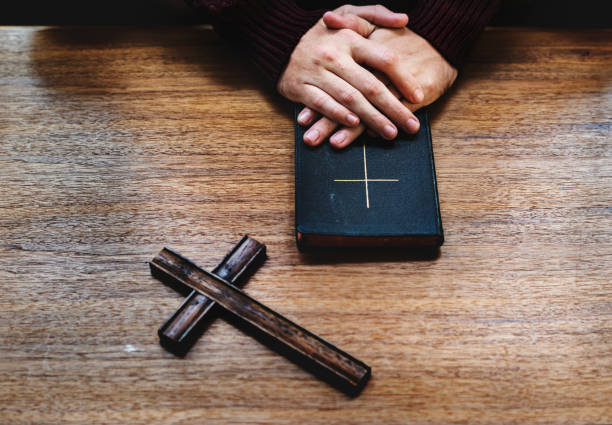 Hands over bible on wooden table Hands over bible on wooden table clergy stock pictures, royalty-free photos & images