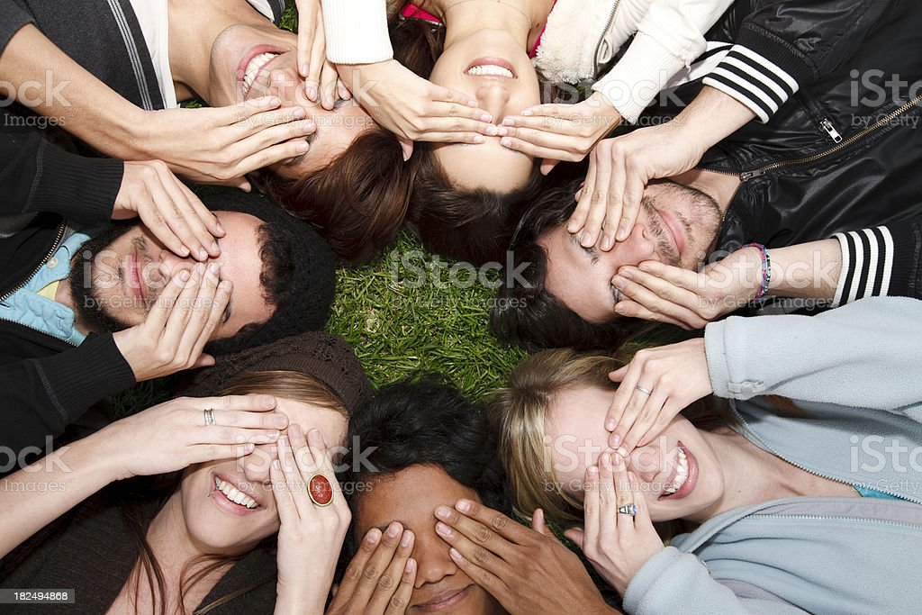 Hands Over Eyes, Young Adults Lying On the Grass royalty-free stock photo