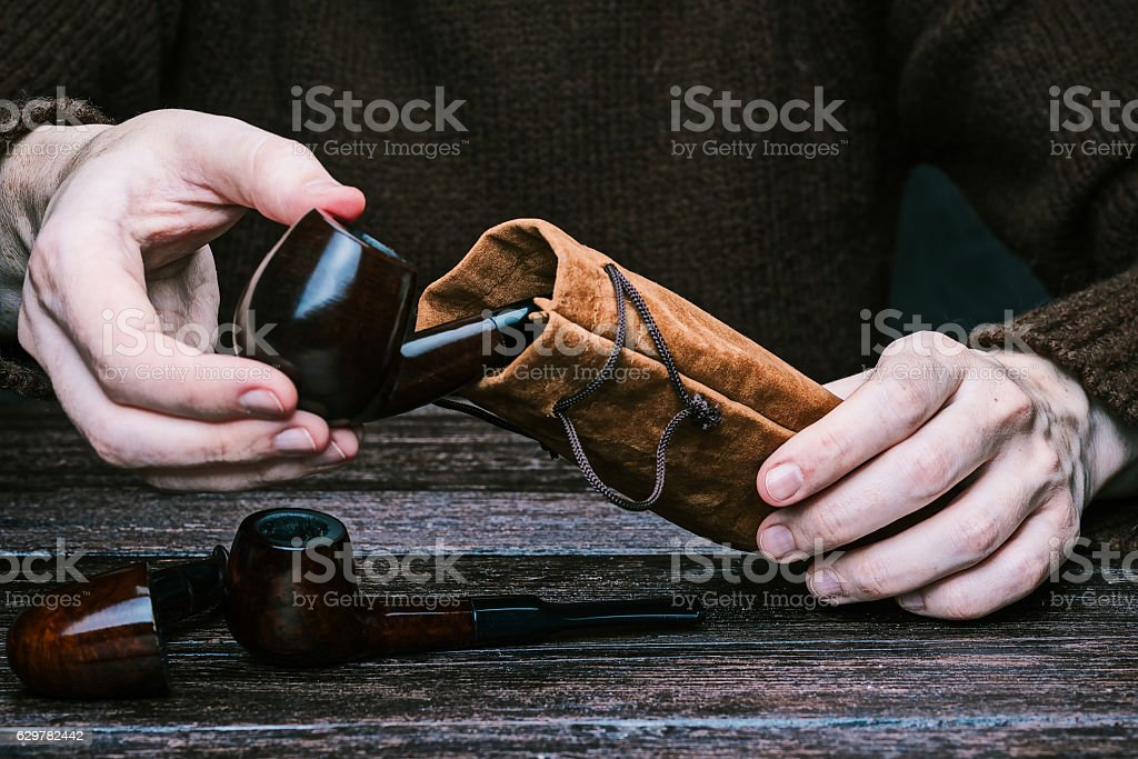 Hands packing smoking pipes stock photo
