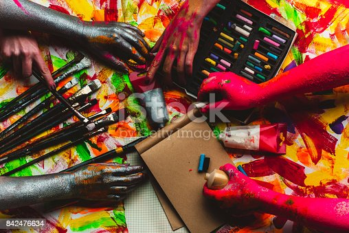 istock Hands, paint, art in art studio, colorful creative background. Red and silver hands paint picture on kraft paper. Modern art and art therapy, drawing lessons at school. Pastel pencils and watercolors 842476634