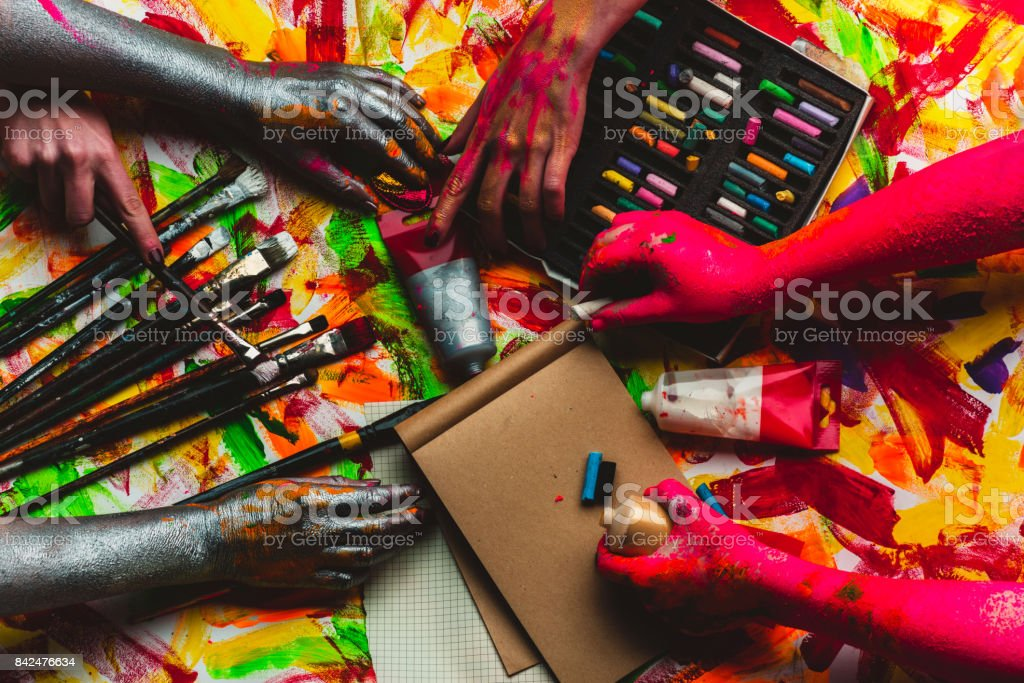 Hands, paint, art in art studio, colorful creative background. Red and silver hands paint picture on kraft paper. Modern art and art therapy, drawing lessons at school. Pastel pencils and watercolors stock photo