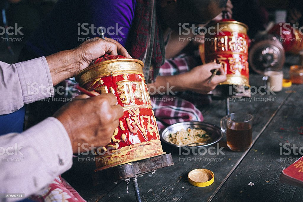Hands painting the prayer wheels in a monastery. stock photo