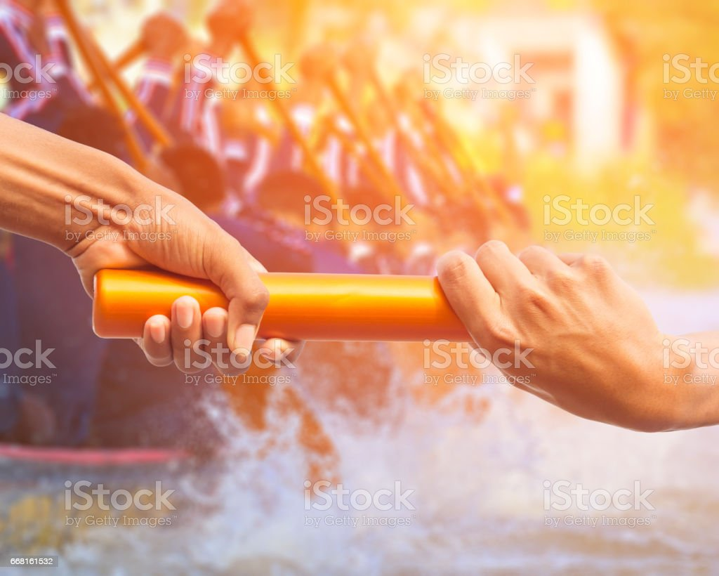 hands passing a relay baton on rowing team background and color tone effect. – Foto