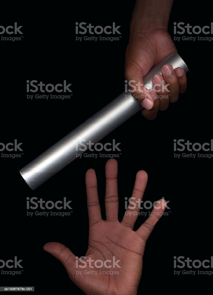 Hands passing baton, close-up, studio shot royalty-free stock photo