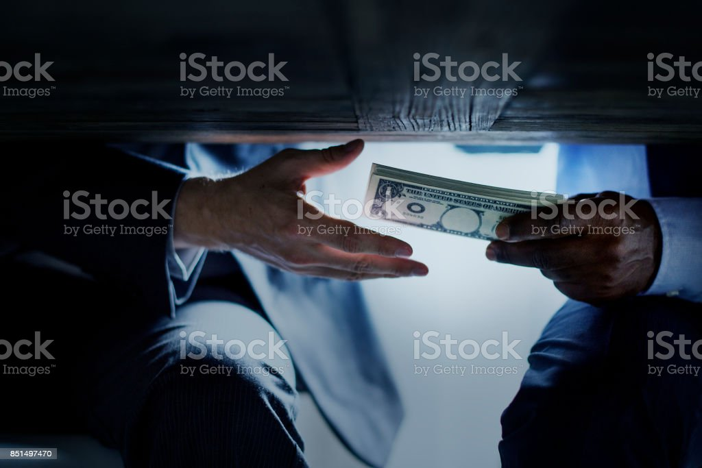 Hands passing money under table corruption bribery stock photo