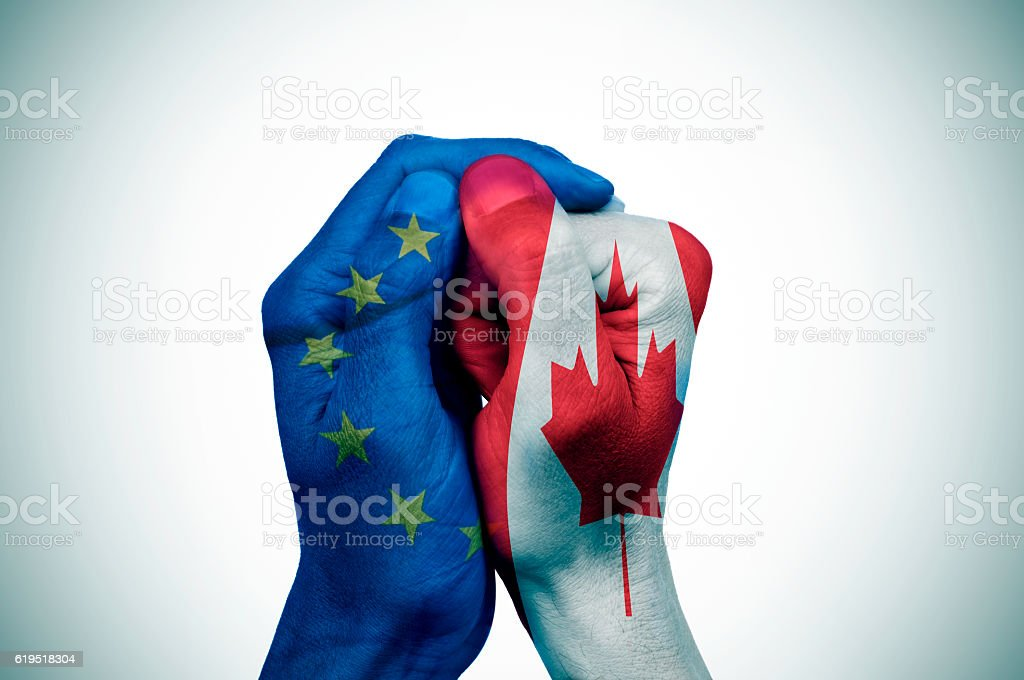 hands patterned with the European and the Canada flags stock photo