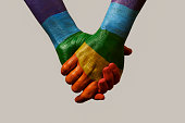 closeup of two men holding hands, painted as the rainbow flag, against an off-white background