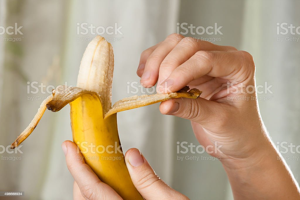 hands peeling a banana stock photo