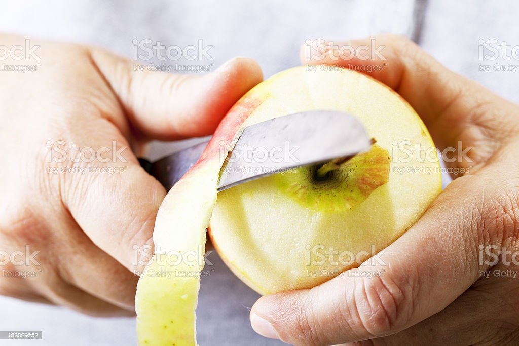 hands peeling an apple royalty-free stock photo