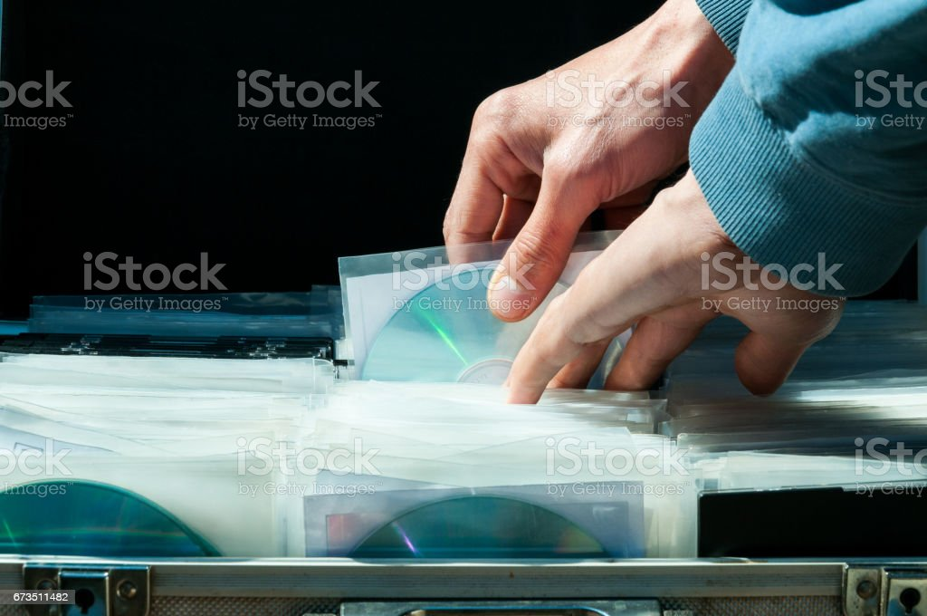Hands pick up CD from metal suitcase full of movie and music piracy CD selling illegally on the street black market. stock photo