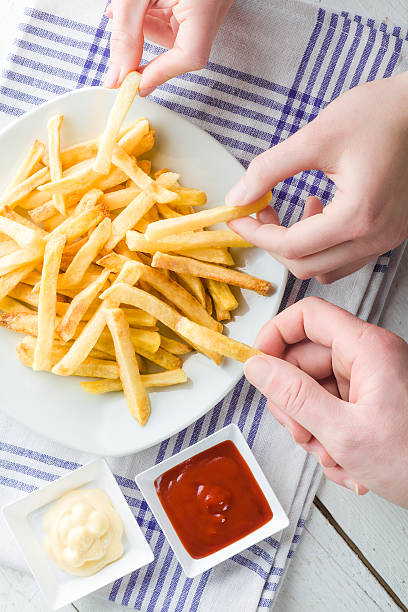 Hands Picking French Fries stock photo