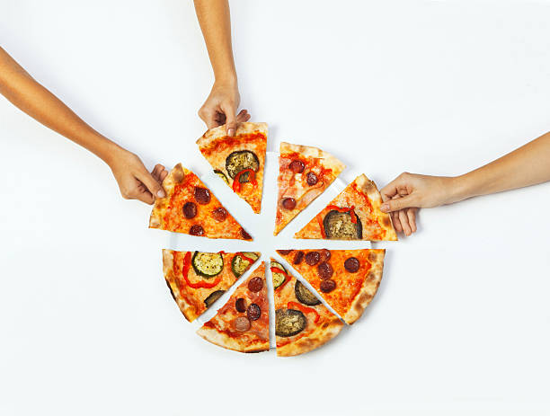 Hands picking portions of pizza stock photo