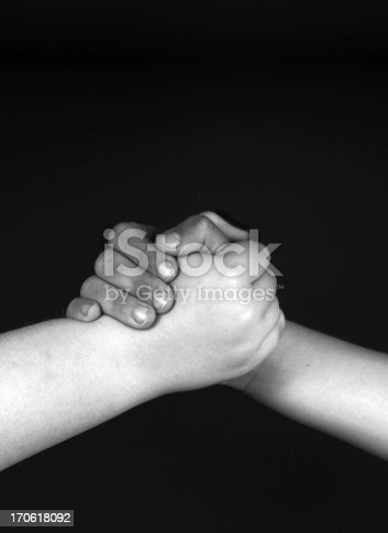 Two young people of different racial origin, holding hands in a greeting gesture.For more like this: