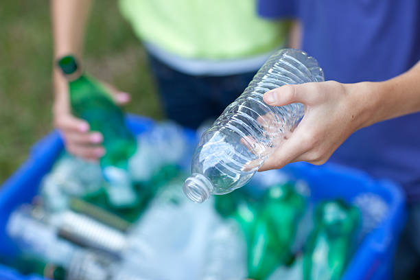 Hands placing bottles in recycling bin Caucasian boy and girl putting clear and green bottles and metal cans in recycling blue bin outside in yard recycling stock pictures, royalty-free photos & images