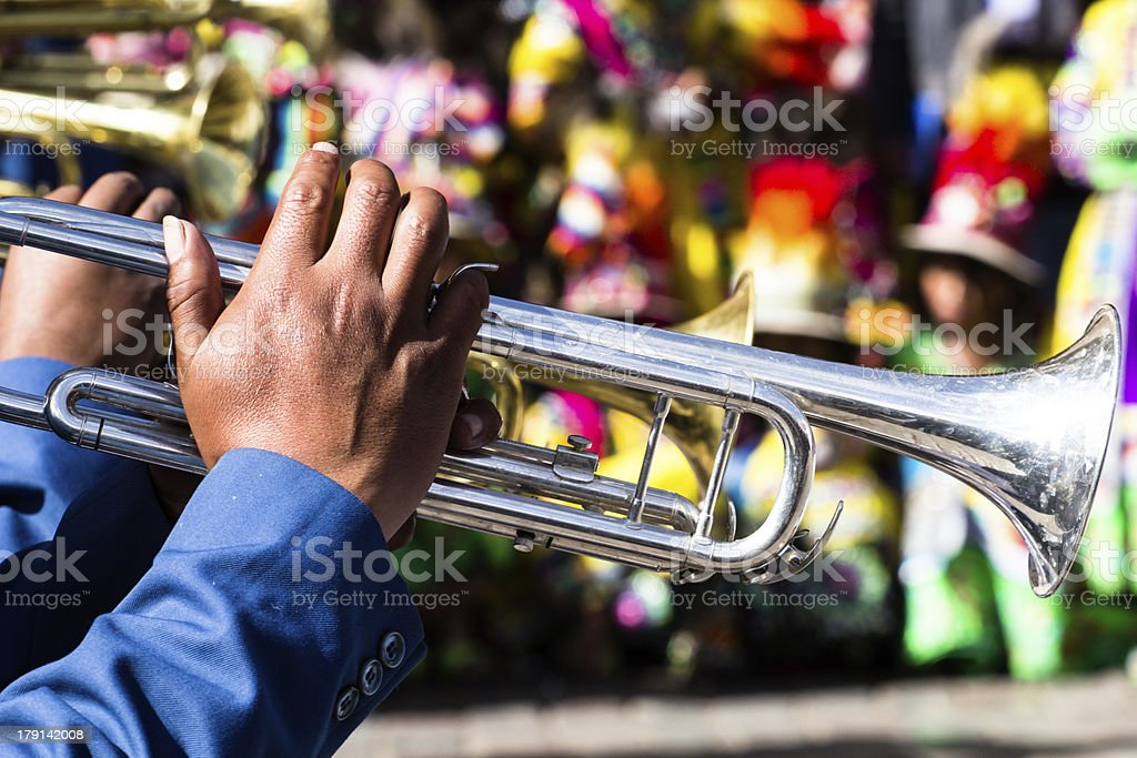 Hands playing a silver trumpet in a Peruvian parade in Cusco stock photo