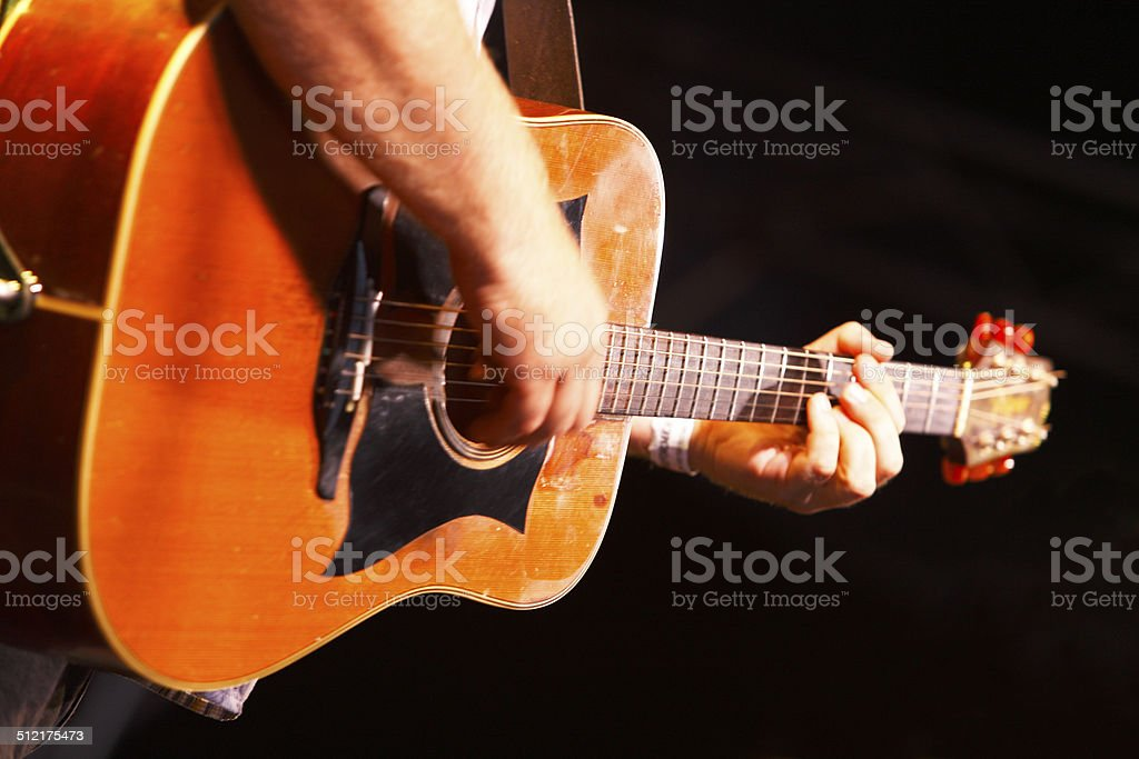 Hands playing acoustic guitar stock photo