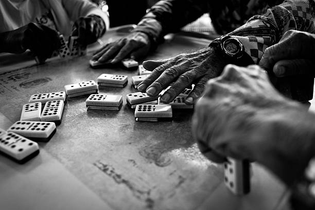 Hands playing dominos stock photo