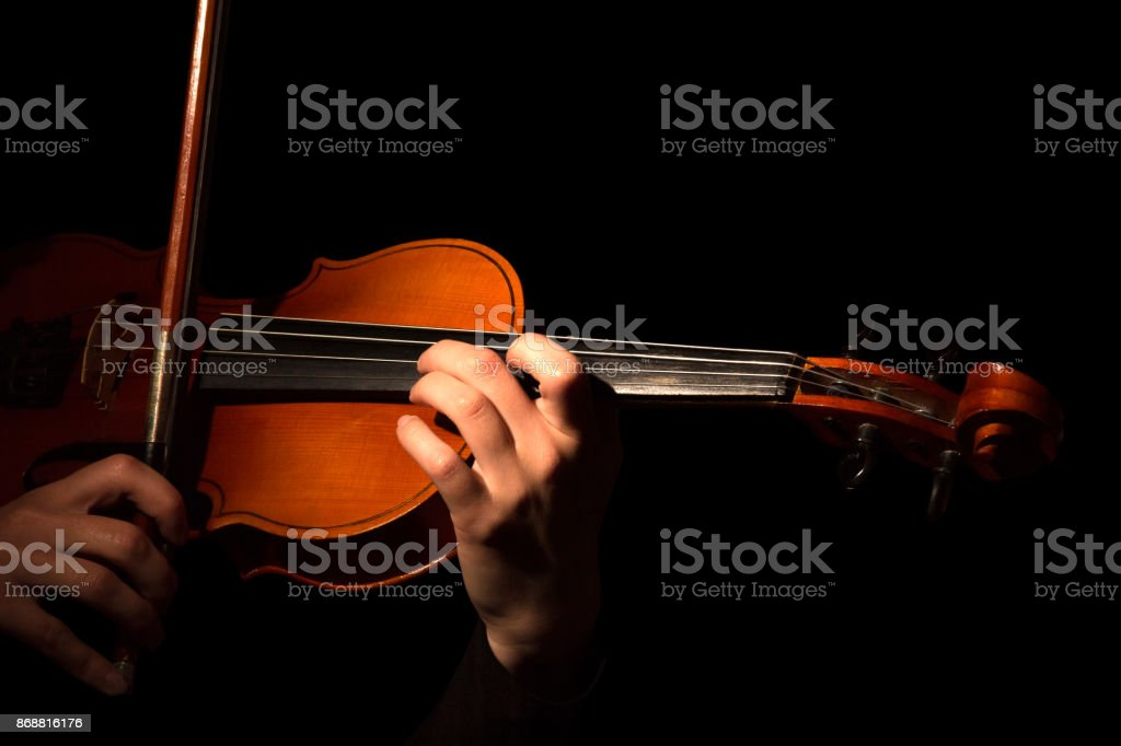 Hands playing the violin isolated on black stock photo