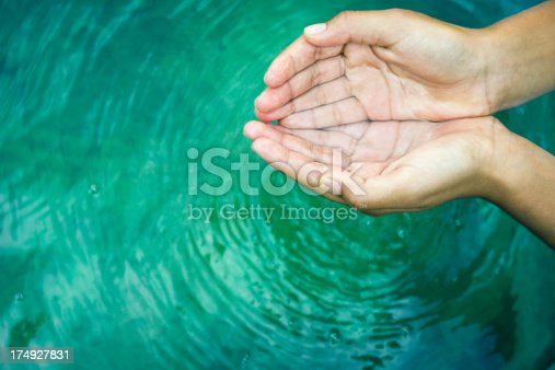 Woman's hands playing with fresh water from fountain.