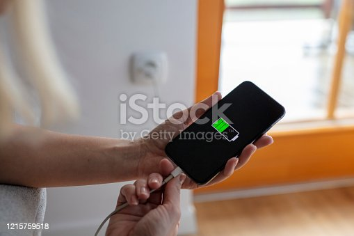 Hands plugging in and charging smart phone with USB cable at wall