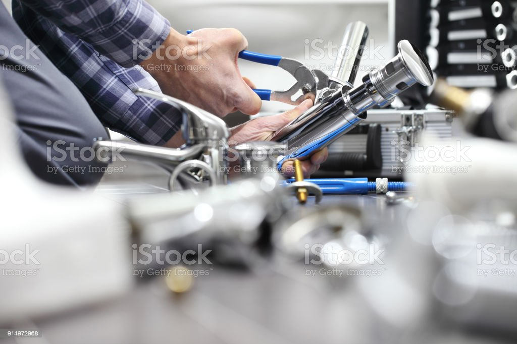 hands plumber at work in a bathroom, plumbing repair service, assemble and install concept stock photo