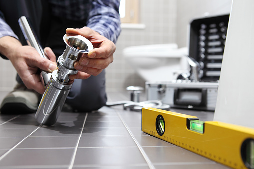 istock hands plumber at work in a bathroom, plumbing repair service, assemble and install concept 918319038