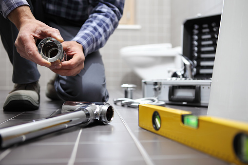 istock hands plumber at work in a bathroom, plumbing repair service, assemble and install concept 918319054