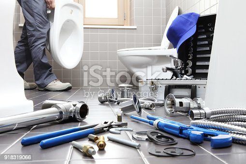 istock hands plumber at work in a bathroom, plumbing repair service, assemble and install concept 918319066