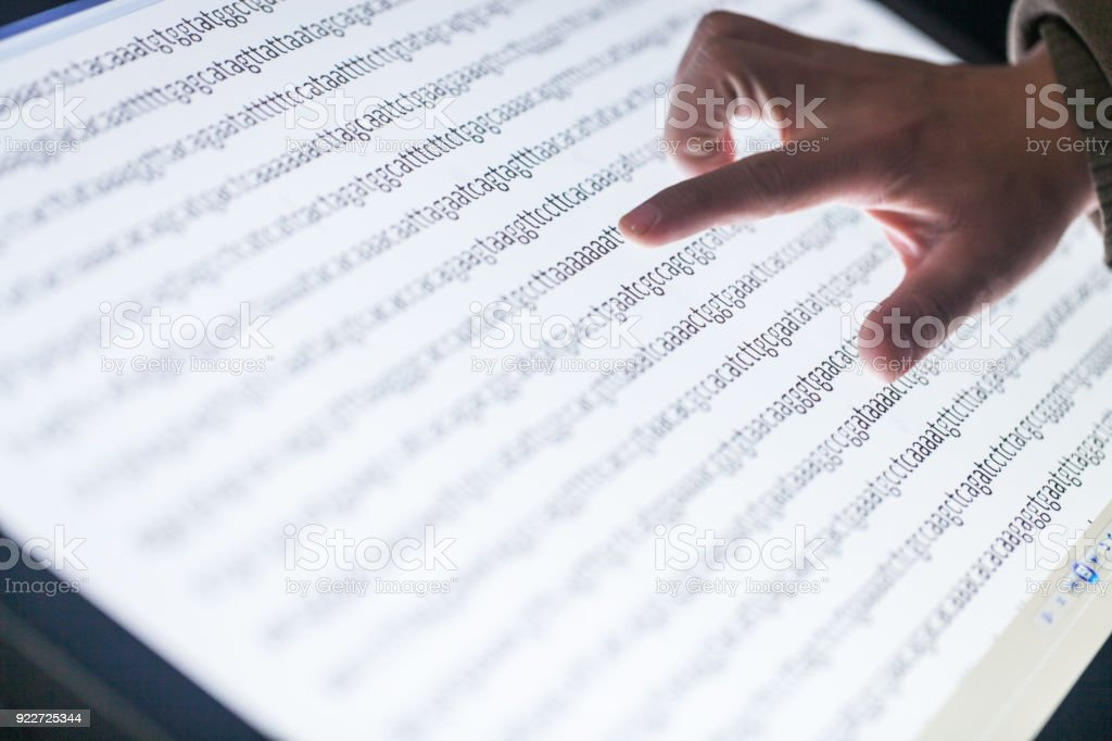 hands point to big screen with DNA sequence code stock photo
