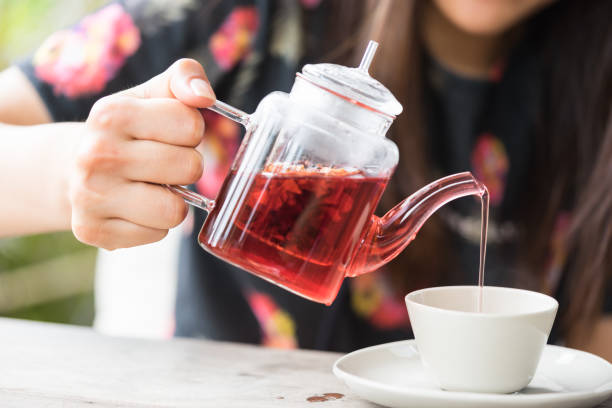 Hands pouring tea from a teapot into a cup stock photo