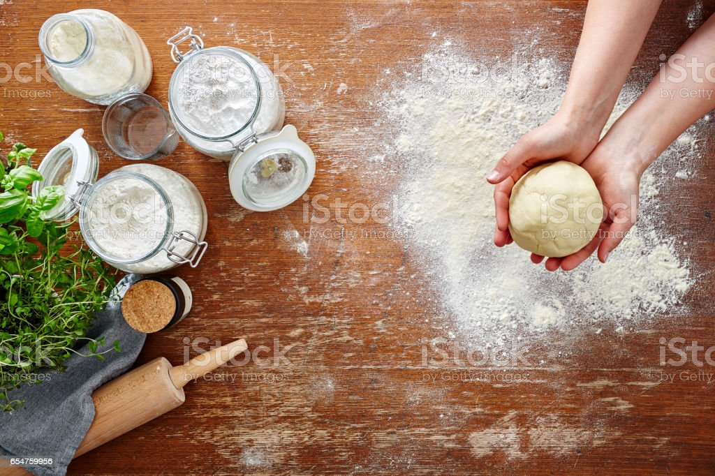 hands presenting pasta dough wooden table and flour stock photo