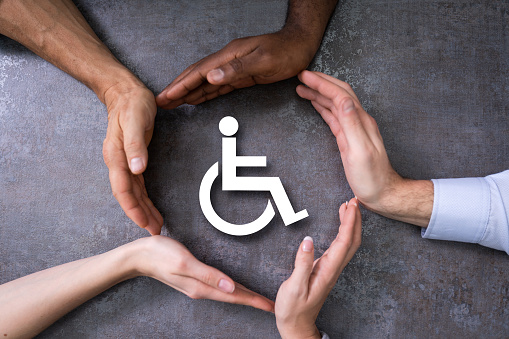 Close-up Of A Hands Protecting Disabled Handicap Icon