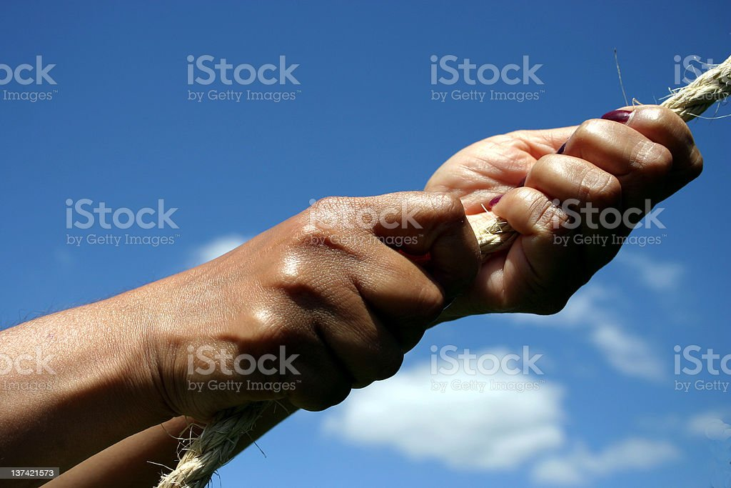 Hands pulling on rope stock photo