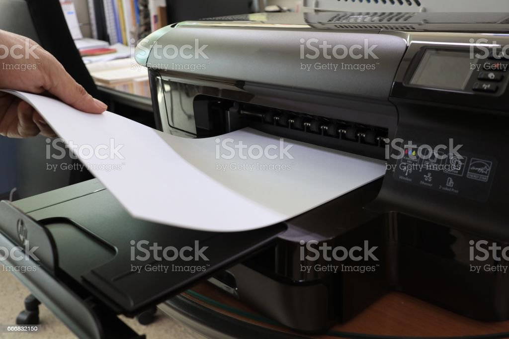 Hands pulling printouts from office printer stock photo